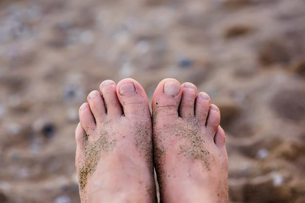 Мужские пальцы ног на фоне песка