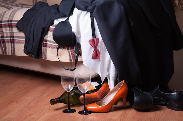 Men's, women's clothes and shoes are scattered on the couch after the party. an empty wine bottle and glasses stand on the floor