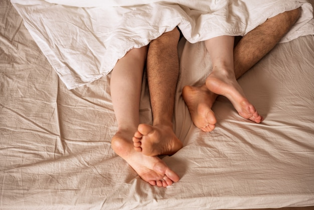 Men's and women's legs stick out from under the blanket.