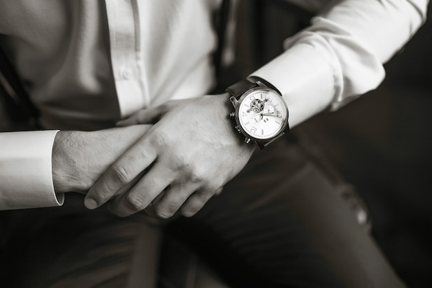Men's wrist watch, the man is watching the time. businessman clock, businessman checking time on his wristwatch. groom's hands in a suit adjusting wristwatch, groom accessories.