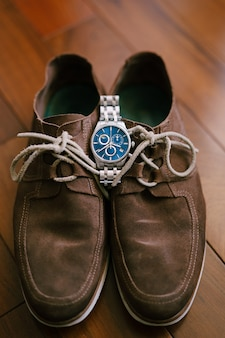 茶色のメンズスエードシューズの上にメンズ腕時計