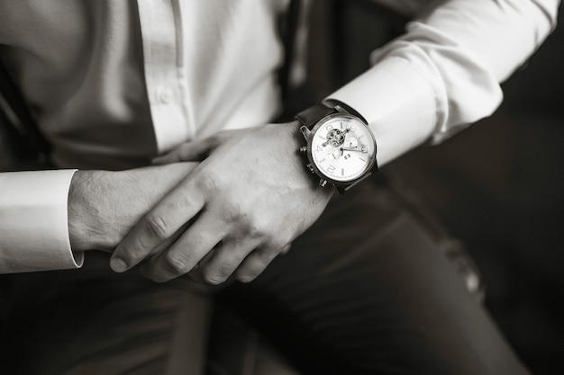 男性用腕時計、男性は時間を監視しています。ビジネスマンの時計、彼の腕時計で時間をチェックするビジネスマン。スーツを着た新郎の手が腕時計、新郎のアクセサリーを調整します。