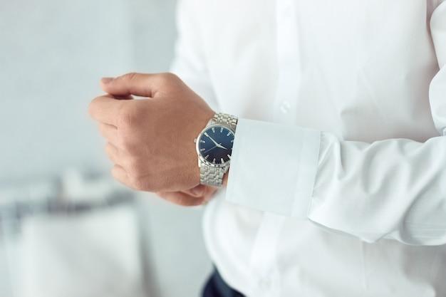 남자 손목 시계, 남자가 시간을보고있다. 사업가 시계, 사업가 자신의 손목 시계에 시간을 확인.