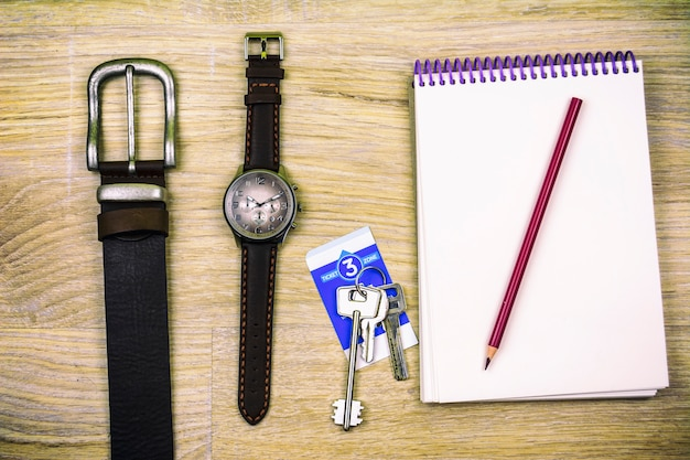 Men's wristwatch, jeans belt, notebook, pencil and padlock keys lie on the wood texture
