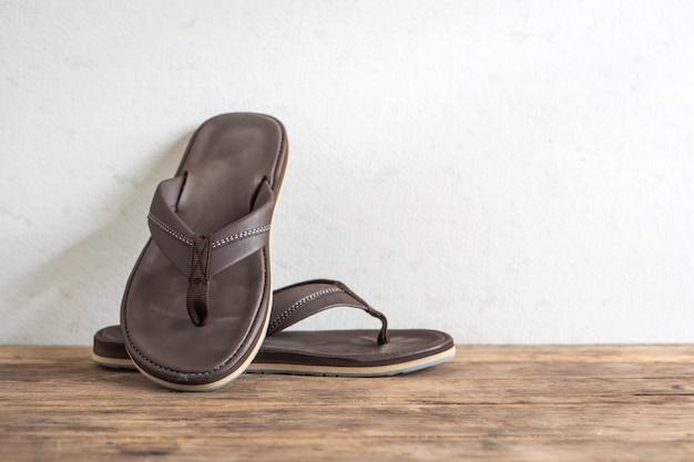 Men sandals footware brown on wood grunge table desk.