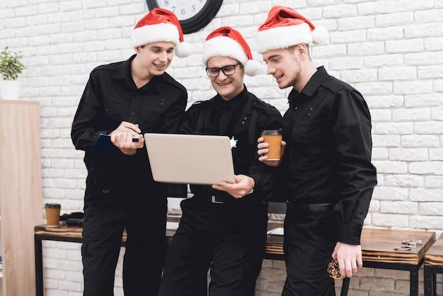 Men in santa claus caps are looking at laptops.