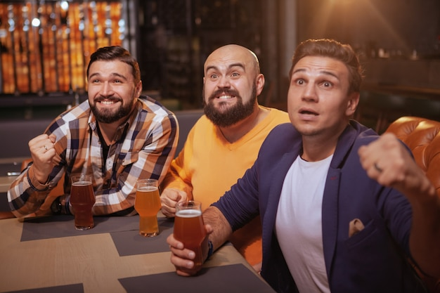 Мужчины кричат во время просмотра футбольного матча в пивном пабе