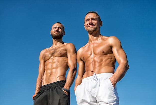 Стойка сексуального мускулистого голого торса мужчин на открытом воздухе. мускулистое тело мужчины уверенно позирует с руками в карманах. спортсмены позируют мускулистым животом. спорт и уход за телом. мускулистые, мужественные парни выглядят уверенно.