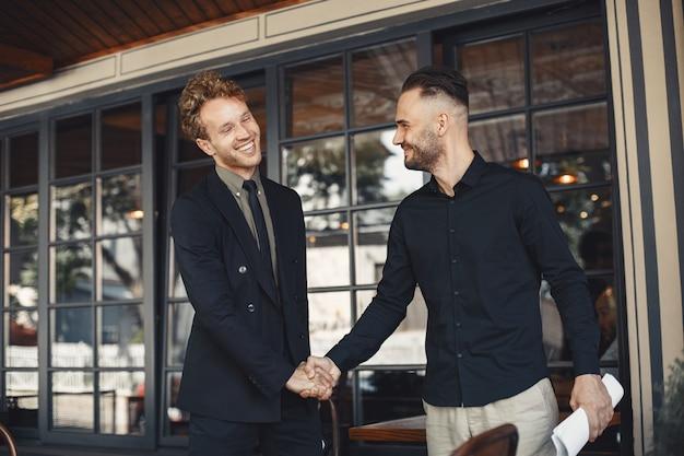 Мужчины пожимают друг другу руки. приложение к деловому соглашению. взаимопонимание между деловыми партнерами.