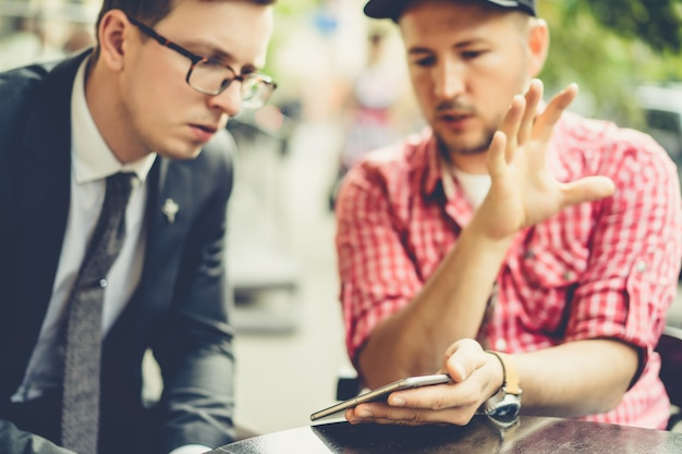 남자들은 스마트 폰에서 뉴스, 사진, 비디오를 공유합니다. 남자는 친구에게 휴대 전화의 응용 프로그램을 보여줍니다. 스마트 폰, 기술 친구.