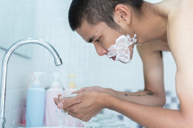 男性は顔を剃る。