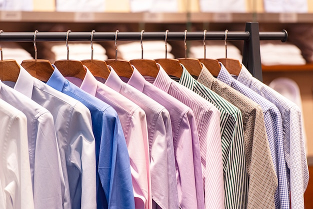 Men shirts on hanger, row of colorful shirts in shopping mall