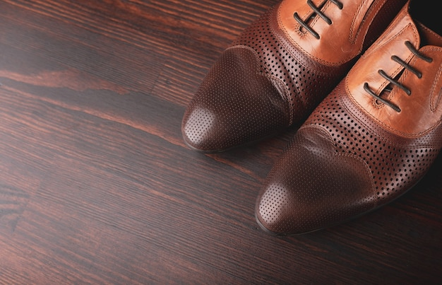 Men shoes on brown wooden surface
