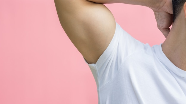 Men showing his armpit on a pink background.