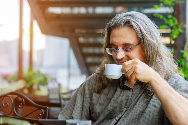 Men sitting in the at drinking coffee and using laptop