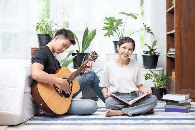 男性はギターを座って、女性は本を持ち、歌います。