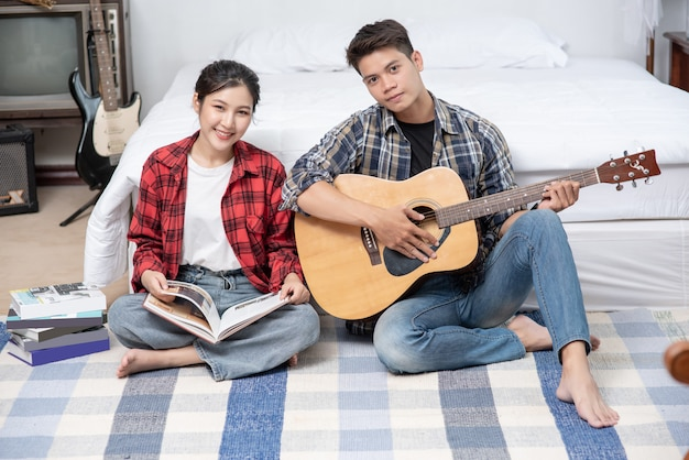 Мужчины сидят на гитаре и женщины держат книги и поют.