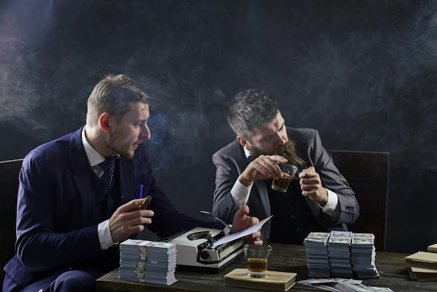 Men sitting at table with piles of money and typewriter illegal business concept businessmen discussing illegal deal while drinking and smoking dark background company engaged in illegal business