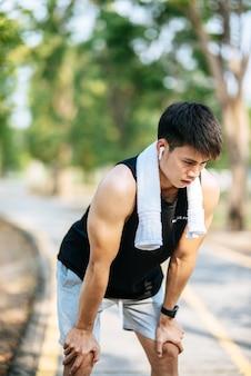 男性は立って、お辞儀をして道端で運動した後休憩します。
