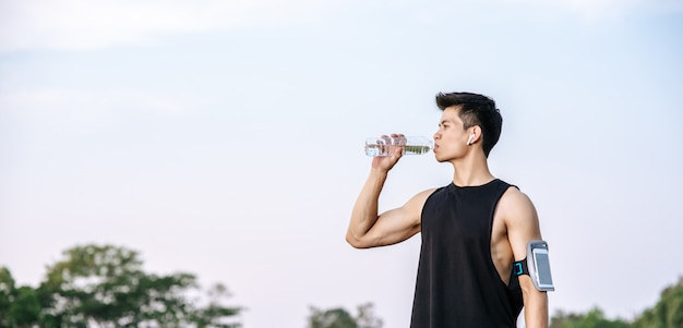 Men stand to drink water after exercise
