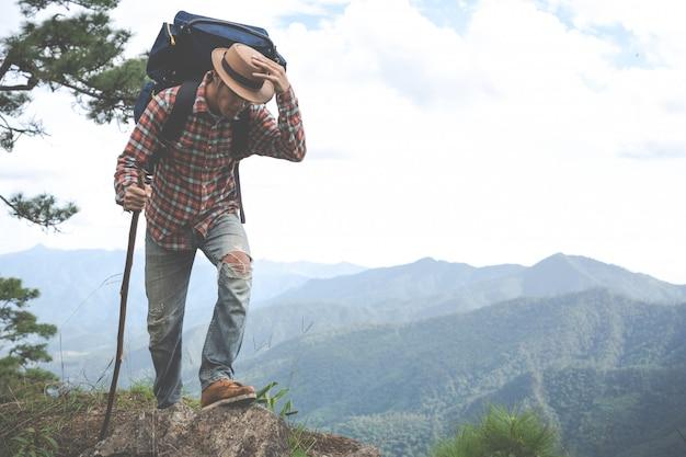 男性は、森のバックパックで熱帯林の山を見るために立ちます。冒険、旅行、登山。