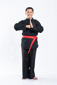 プンチャックシラットのユニフォームを着て立って笑っている男性は、敬意を表して手の動きで立ち上がる