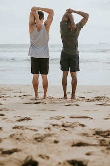 Men stretching on the beach