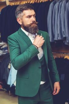 衣料品店のショーケースにスーツを着た男性。緑のスーツを着ているひげを生やした白人男性。古典的なスーツのハンサムなひげを生やした実業家。店内のスーツの列に対して古典的なベストの男。広告写真