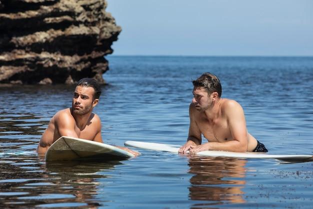 海で一緒にサーフィンする男性
