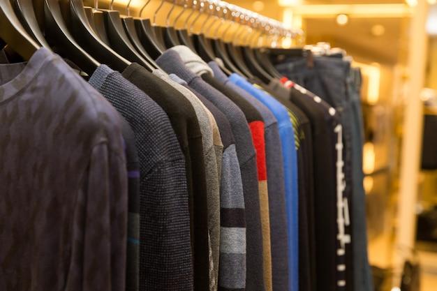 소매 옷가게의 옷걸이에 다양한 색상의 남성용 스웨터와 셔츠.