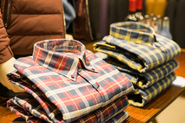 Men sweaters and shirts in different colors on hangers in a retail clothes store