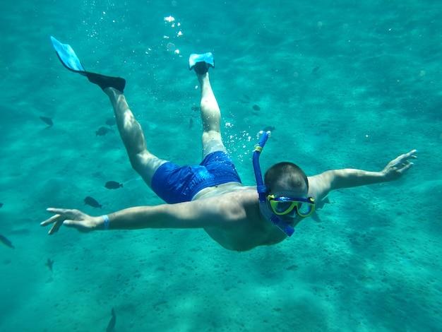 Men swim underwater in masks on the sea