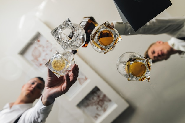 Men take glasses with whisky from a glass table
