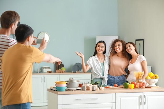 부엌에서 요리하는 그들의 친구의 사진을 복용하는 남자