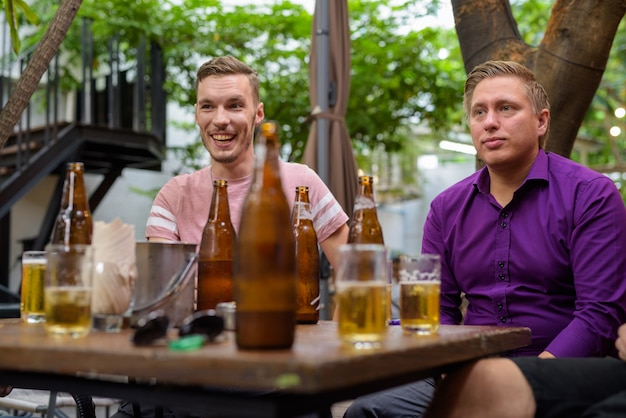 Men talking and laughing while drinking beer outdoors