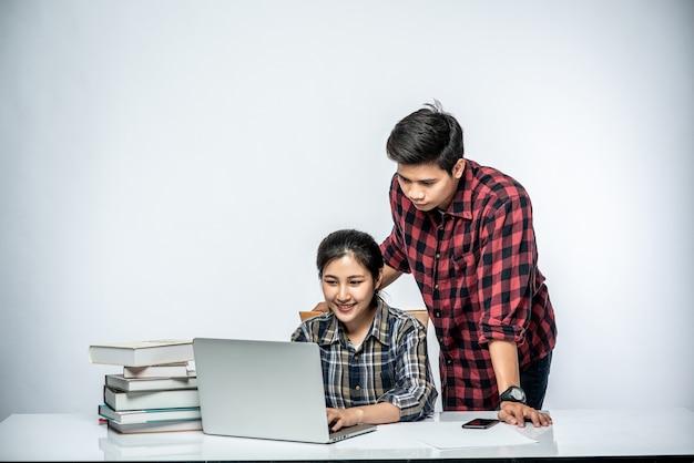 男性は女性に職場でのラップトップの使い方を教えています。