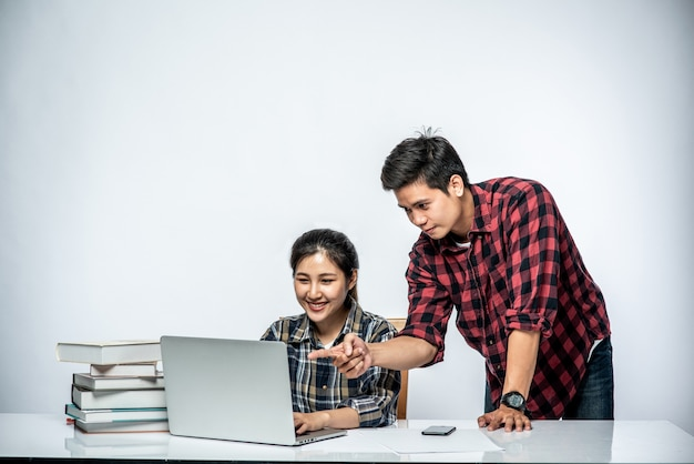 Men teach women how to work with laptops at work.