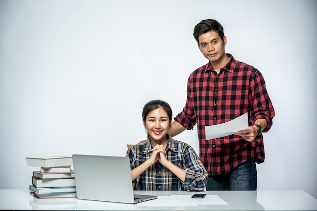 Gli uomini insegnano alle donne come lavorare con i laptop al lavoro.
