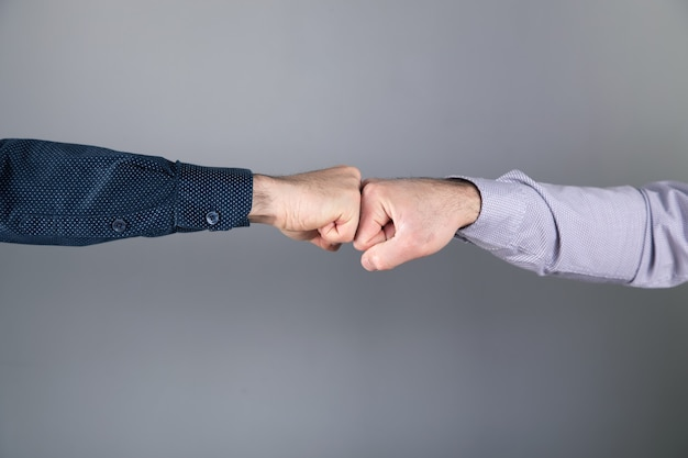 Men touch with fists on gray surface .
