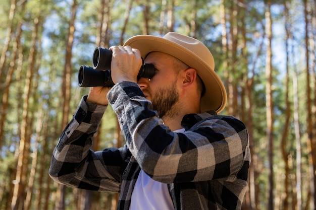 Men tourist in a hat and a gray checkered shirt looks through binoculars on a forest background.