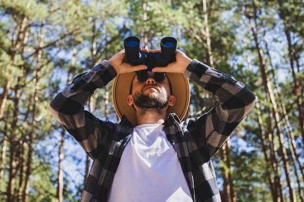 帽子と灰色の市松模様のシャツを着た男性観光客は、森の背景に双眼鏡を通して見ています。