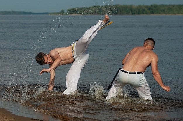 Men train capoeira on the beach