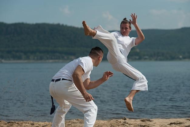 Men train capoeira on the beach