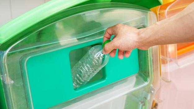 Men trash an empty bottle in a bin.