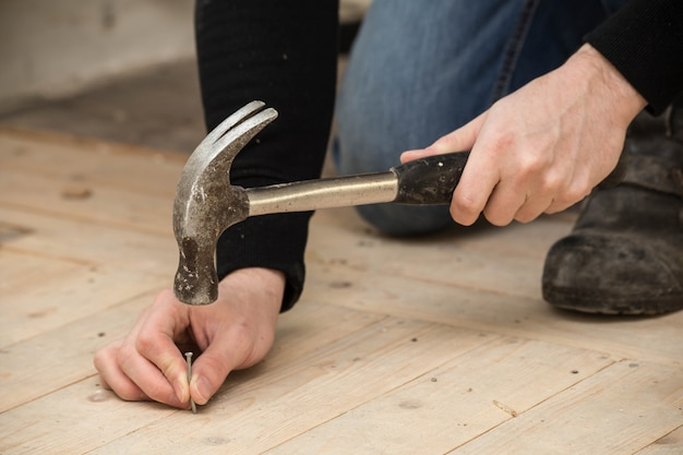 Men using a hammer and nail on wood , renovation concept
