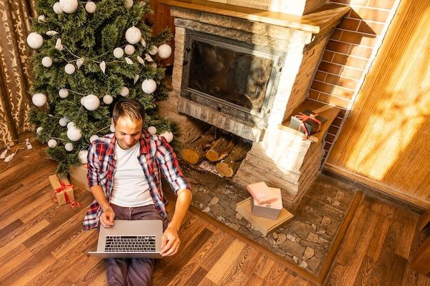 Мужчины, использующие ноутбук в старом деревянном доме во время рождественских праздников