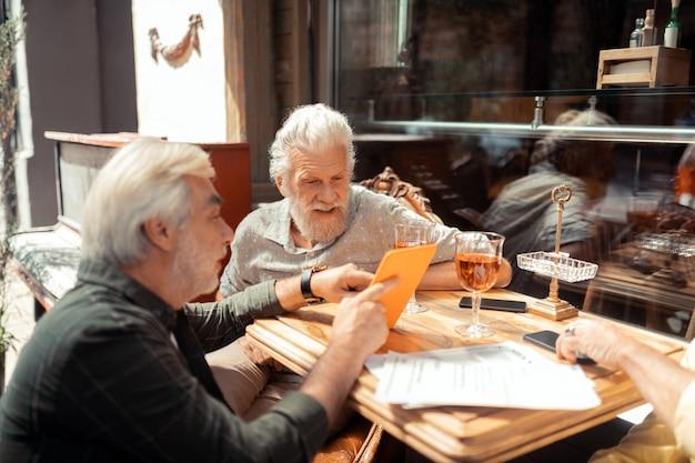 태블릿을 사용하는 남성. 주말에 밖에서 이야기하고 술을 마시는 동안 태블릿을 사용하는 수염 난 남자