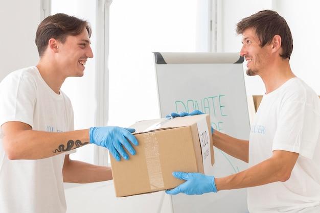 Мужчины добровольно делают пожертвования для бедных
