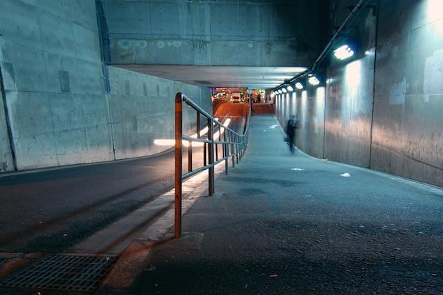 暗闇の中で進行中のトンネルを歩いている男性、大阪、日本
