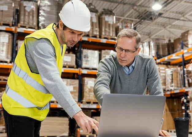 Uomini in magazzino che lavorano al computer portatile